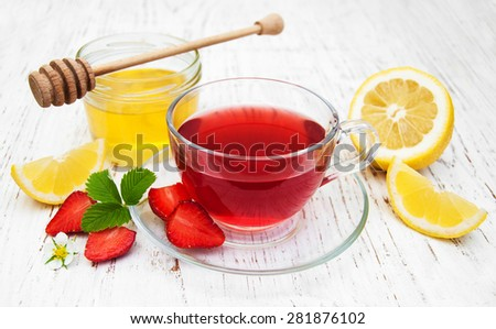 Fruit tea with strawberries and honey on a wooden table - stock photo