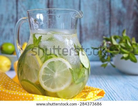 Fruit water with lemon, lime, cucumber and mint in glass pitcher - stock photo