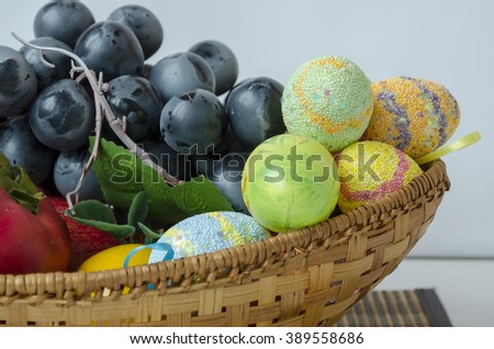 Fruits and colorful Easter eggs in a basket