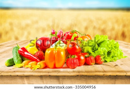 fruits and vegeetables on wooden desk and autumn field on background - stock photo