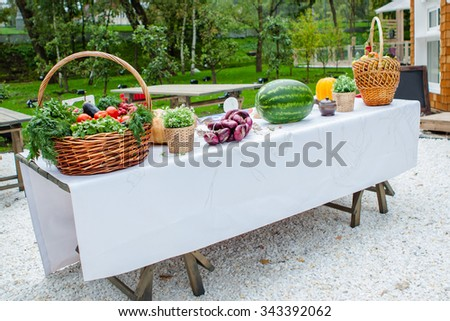 Fruits and vegetables in a basket, standing on a table covered with a white cloth - stock photo
