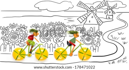Fruits and vegetables in the shape of women cyclists riding bikes in the country. - stock photo