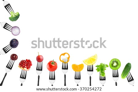 Fruits and vegetables on fork on white background