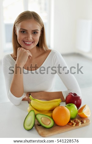 Fruits. Beautiful Smiling Woman Sitting At Table With Fresh Juicy Organic Fruits On It. Portrait Of Attractive Happy Girl In Kitchen With Healthy Food. Nutrition And Vitamins Concept. High Resolution