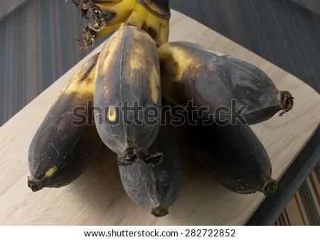 Fruits, Black Rotten Wild Banana, Asian Banana or Cultivated Banana on A Wooden Cutting Board. - stock photo