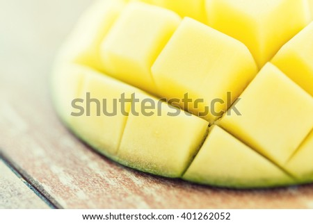 fruits, diet, food and objects concept - close up of ripe mango slice on table - stock photo