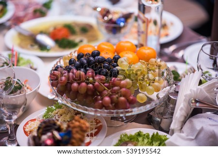 Fruits - Grapes, pears, tangerines. Against the background of the table with appetizers.