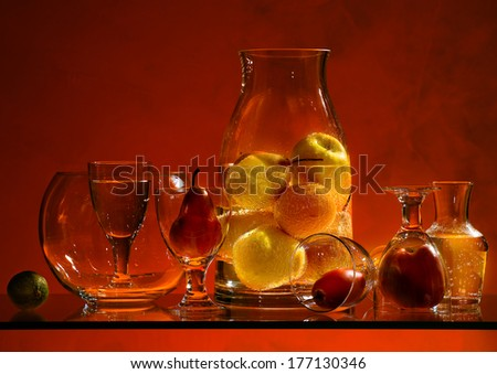 Fruits in glass composition on colored background and reflections