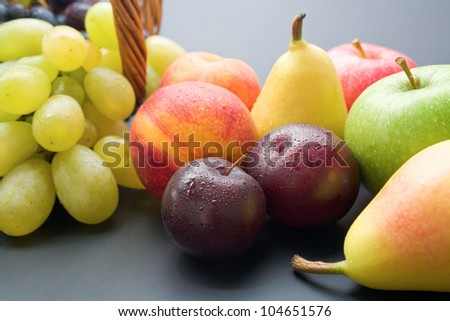 Fruits. Mix of fresh ripe fruits close-up: plums, peaches, pears, apples and grapes on neutral background. - stock photo