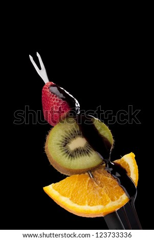 Fruits on a fondue stick with melted chocolate above against dark background - stock photo