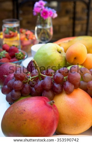 Fruits on a plate: grapes, grapefruit, apple, orange, pomegranate, peach