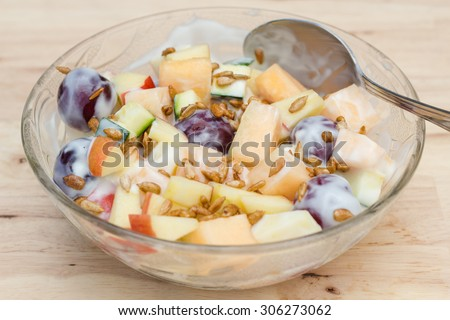 Fruits salad with plain low fat yogurt topping with sunflower seeds honey roasted. - stock photo