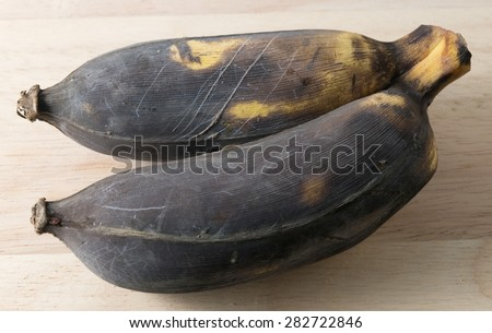 Fruits, Two Black Rotten Wild Banana, Asian Banana or Cultivated Banana on A Wooden Table. - stock photo