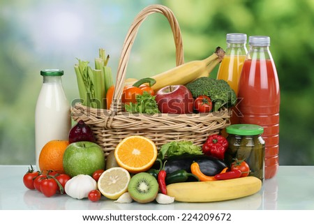 Fruits, vegetables, groceries and beverages in a shopping basket - stock photo