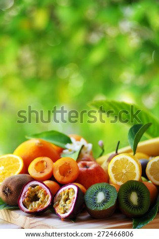 Fruits with leafs on table, green background - stock photo