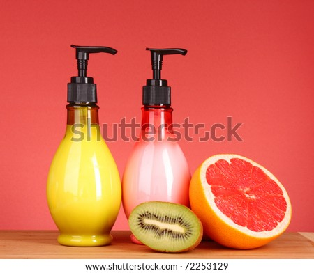 Fruity body lotion, grapefruit and kiwi fruit on a red background - stock photo