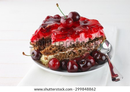 Fruity cake with jelly and cherries in white plate on white background.