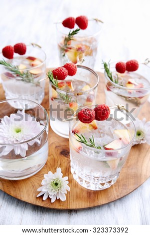 Fruity cocktails/soda water being served on a wooden tray decorated with flowers, raspberries, sliced apples and garnish - stock photo