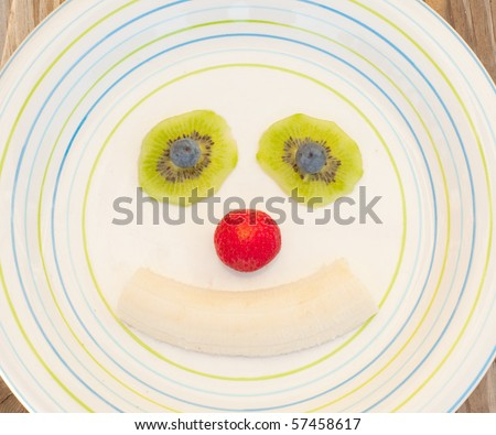 Fruity face smiling clown of strawberry, kiwi, banana and blueberry