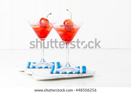 Fruity summer cocktail topped with a fresh whole cherry. - stock photo
