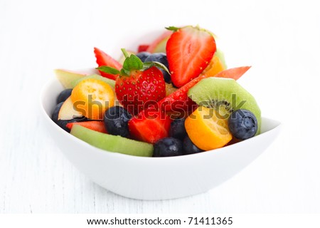Fruity summer salad in white bowl on white background - stock photo