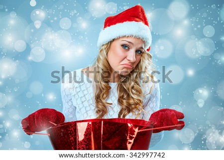 Frustrated and annoyed beautiful young woman in Santa Claus hat with a gift on a blue background - stock photo