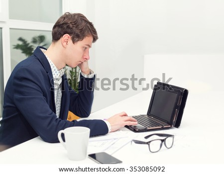 Frustrated and surprised young student man while sitting at his working place in office. Feeling exhausted. He looks at the screen. Working in the office with documents and computer. - stock photo