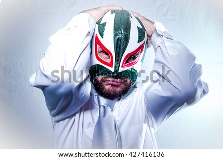Frustrated, angry businessman with Mexican wrestler mask, expressions of anger and rage - stock photo