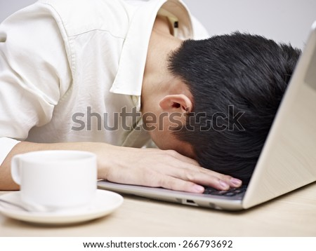 frustrated asian young man buries his head in the keyboard of a laptop computer. - stock photo