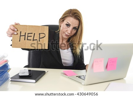 frustrated attractive businesswoman in her 40s holding help sign desparate suffering stress overworked and overwhelmed working at office laptop computer in sad and worried face expression - stock photo