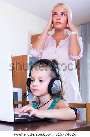 Frustrated blonde woman catching her little daughter watching forbidden site online