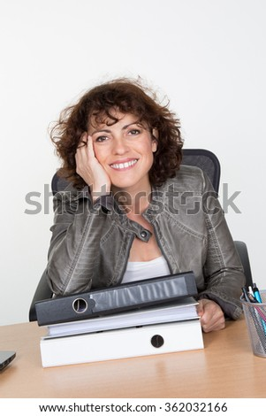 Frustrated business woman in office looks at unbelievable folder stack. Isolated on white background. - stock photo