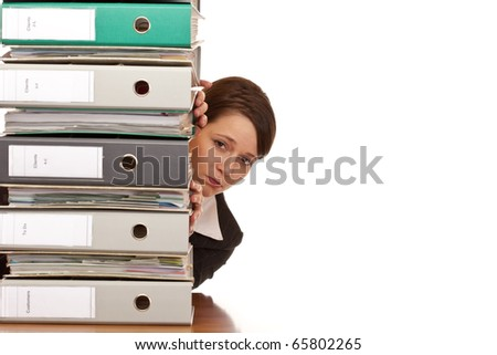 Frustrated business woman looks behind behind a folder stack. Isolated on white background. - stock photo