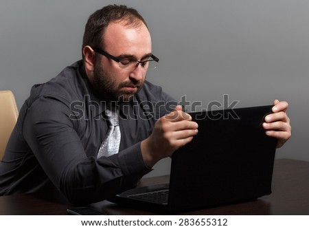 Frustrated businessman gripping his laptop - stock photo