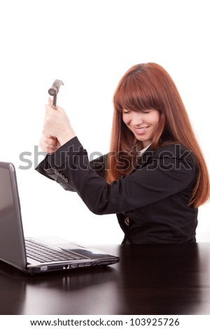 Frustrated businessman in her office threatening to destroy her PC with a hammer out of sheer frustration - stock photo