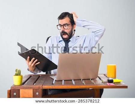 Frustrated businessman in his office with his folder - stock photo
