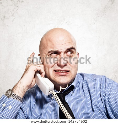 Frustrated businessman in messy situation talking on the phone.