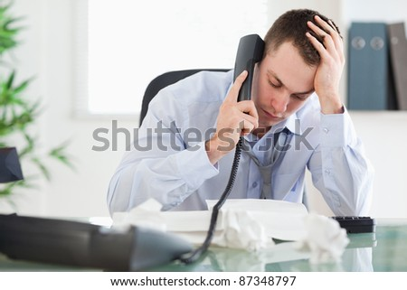 Frustrated businessman looking at an invoice while on the phone