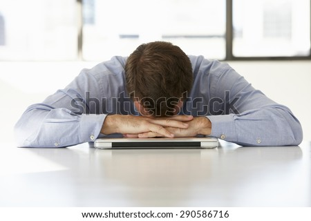Frustrated Businessman Sitting At Desk In Office Using Laptop - stock photo