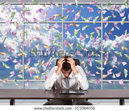 frustrated businessman sitting in office and falling euro bills - stock photo