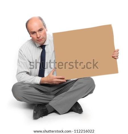 Frustrated businessman with empty sign board. Crisis metaphor. - stock photo