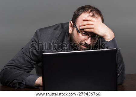 Frustrated businessman working on laptop - stock photo