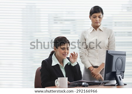 Frustrated businesswoman reading document with female executive - stock photo