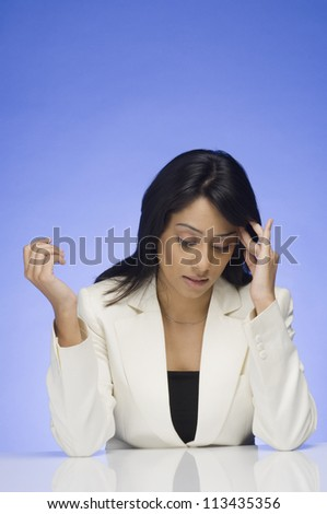 Frustrated businesswoman rubbing her temple - stock photo