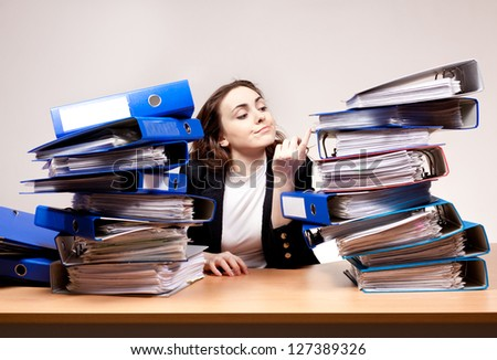 Frustrated businesswoman with stack of folders at office - stock photo