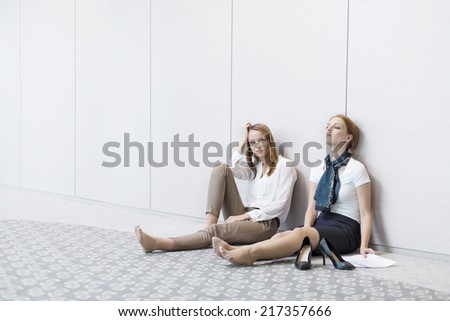 Frustrated businesswomen sitting on floor in office - stock photo