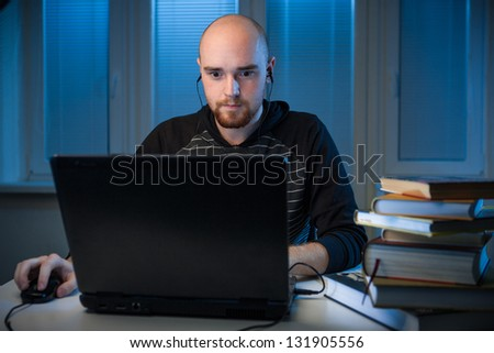 frustrated college student studying poorly at late evening,  playing a video games insead of studying,night before exam, funny night procrastination concept - stock photo