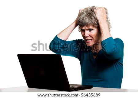 Frustrated computer user tearing out her hair - stock photo