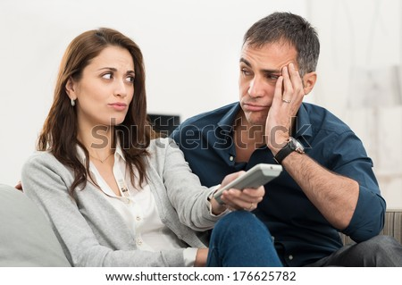Frustrated Couple Looking At Each Other While Watching Television Sitting On Couch - stock photo