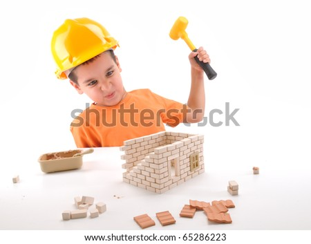 Frustrated cute boy destroying brick house he built  isolated on white - a series of BUILDING A HOUSE  images. - stock photo